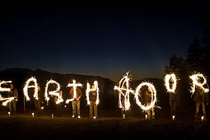 A group of people spelling out Earth Hour with sparklers against a dark sky on Vancouver Island, Earth Hour 2010, Canada.